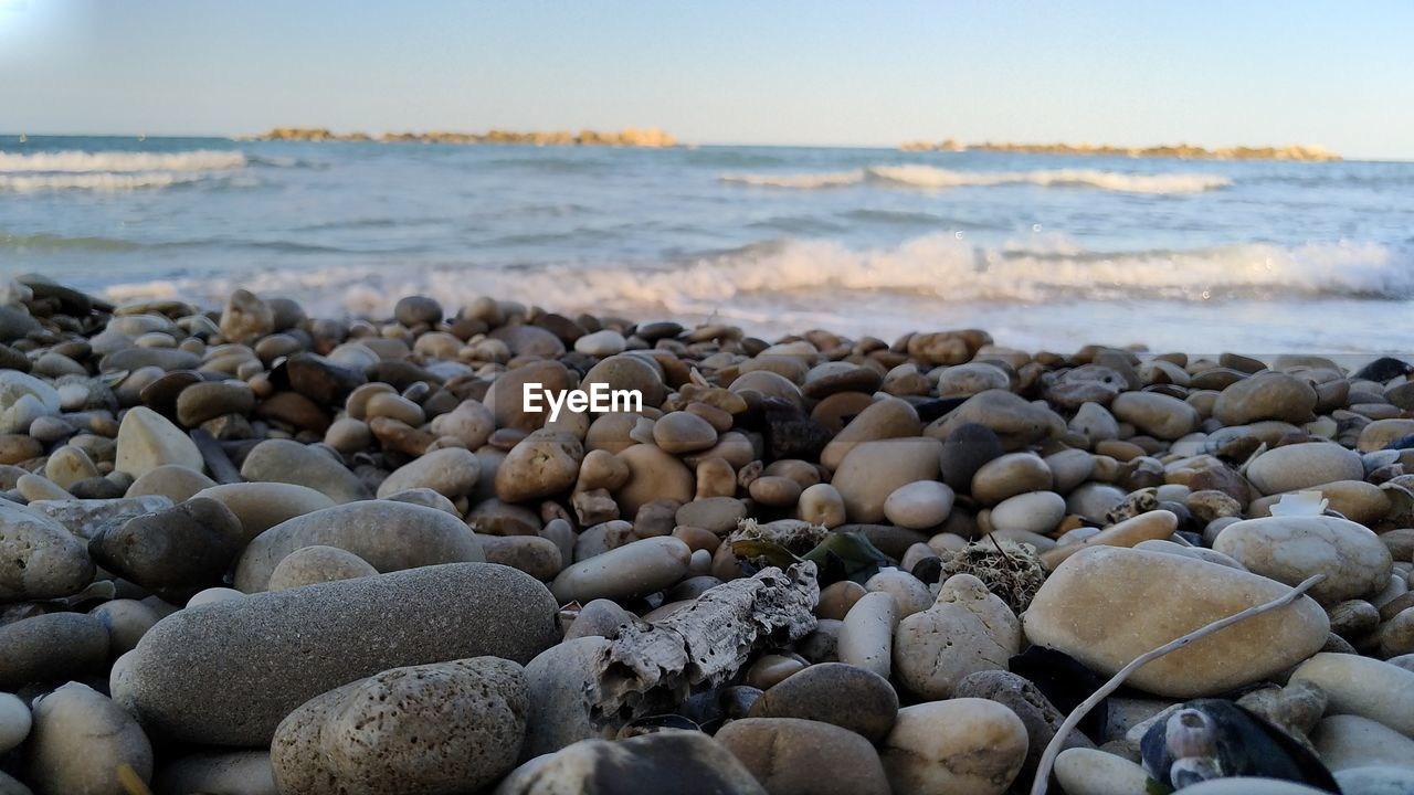 sea, water, beach, rock, solid, pebble, land, stone - object, stone, nature, no people, beauty in nature, tranquility, day, rock - object, scenics - nature, wave, tranquil scene, sky, horizon over water, outdoors