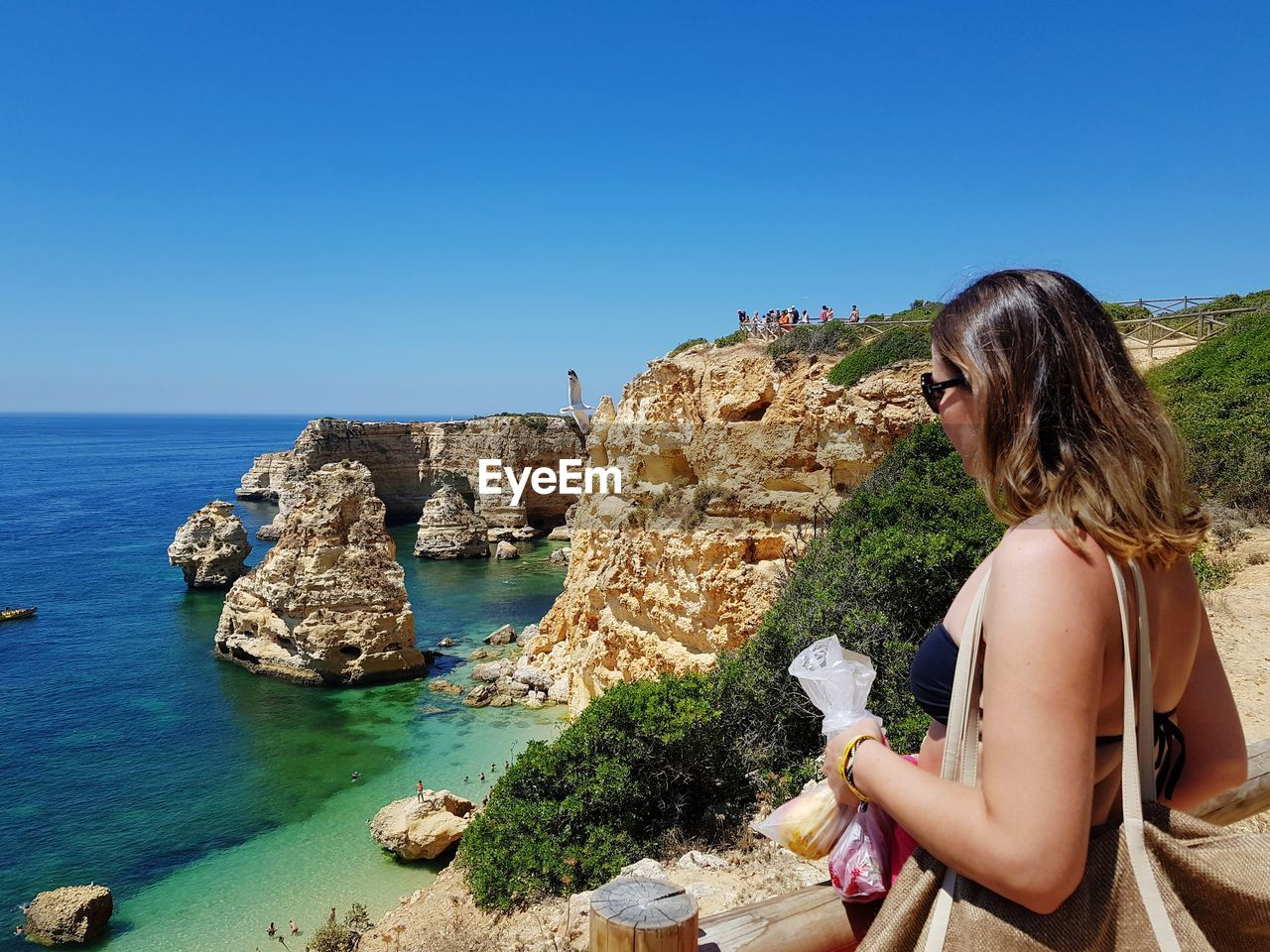 Side view of woman looking at sea on mountain during sunny day