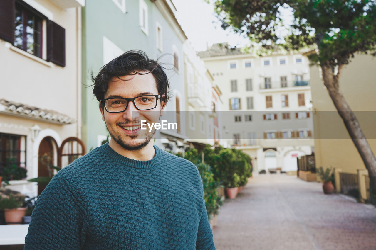 PORTRAIT OF SMILING YOUNG MAN STANDING IN CITY