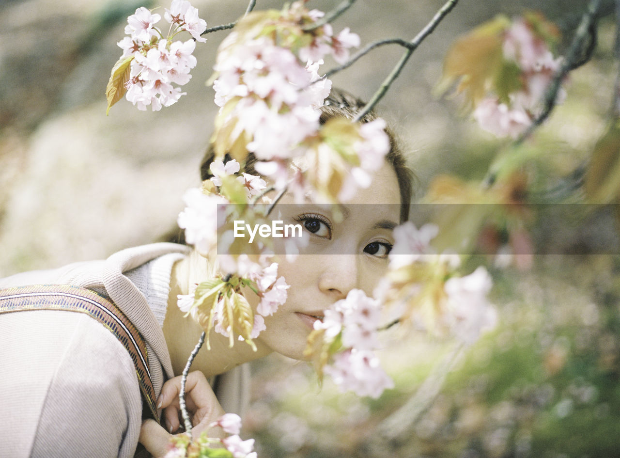 flowering plant, flower, plant, portrait, fragility, vulnerability, freshness, real people, one person, looking at camera, nature, young women, young adult, headshot, lifestyles, women, beauty in nature, leisure activity, day, close-up, flower head, beautiful woman, outdoors, springtime, cherry blossom, flower arrangement, bouquet