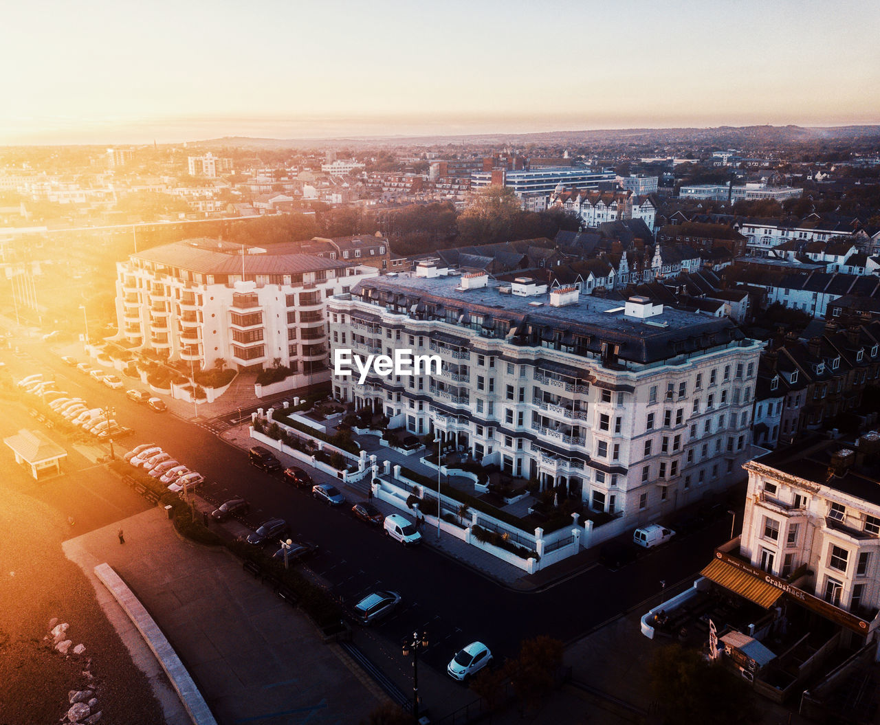building exterior, architecture, city, built structure, cityscape, high angle view, sky, building, nature, street, transportation, no people, residential district, city life, road, mode of transportation, land vehicle, sunset, outdoors, office building exterior, skyscraper