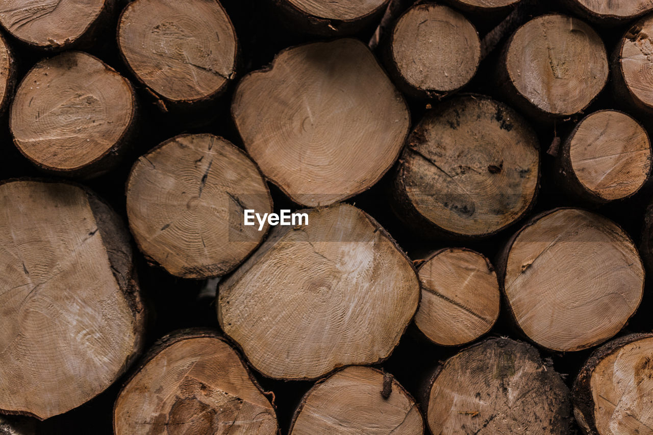 full frame, timber, firewood, log, stack, wood, backgrounds, wood - material, lumber industry, large group of objects, tree, forest, shape, fuel and power generation, heap, abundance, deforestation, no people, brown, design, woodpile