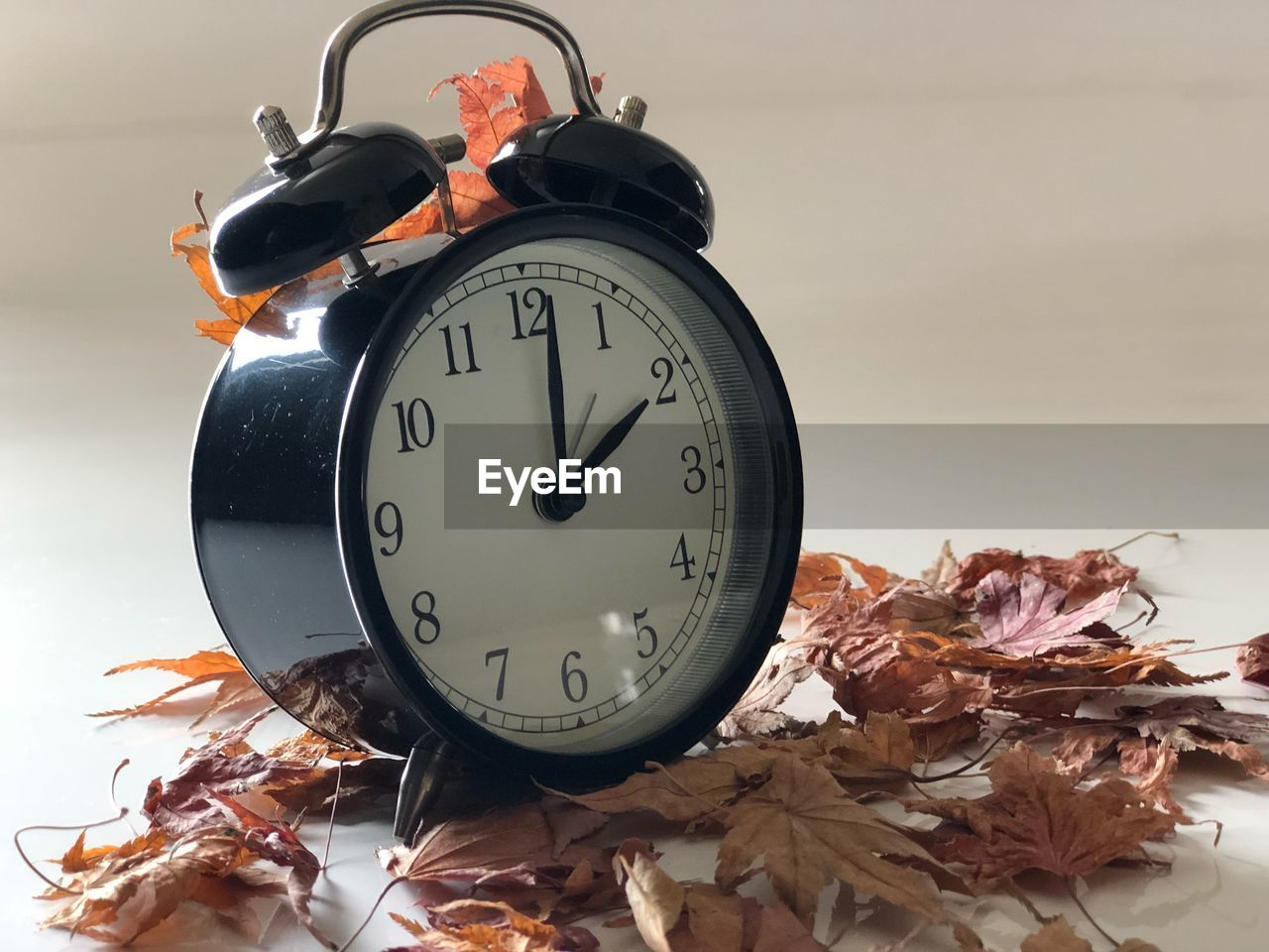 Close-up of alarm clock and dry leaves on table