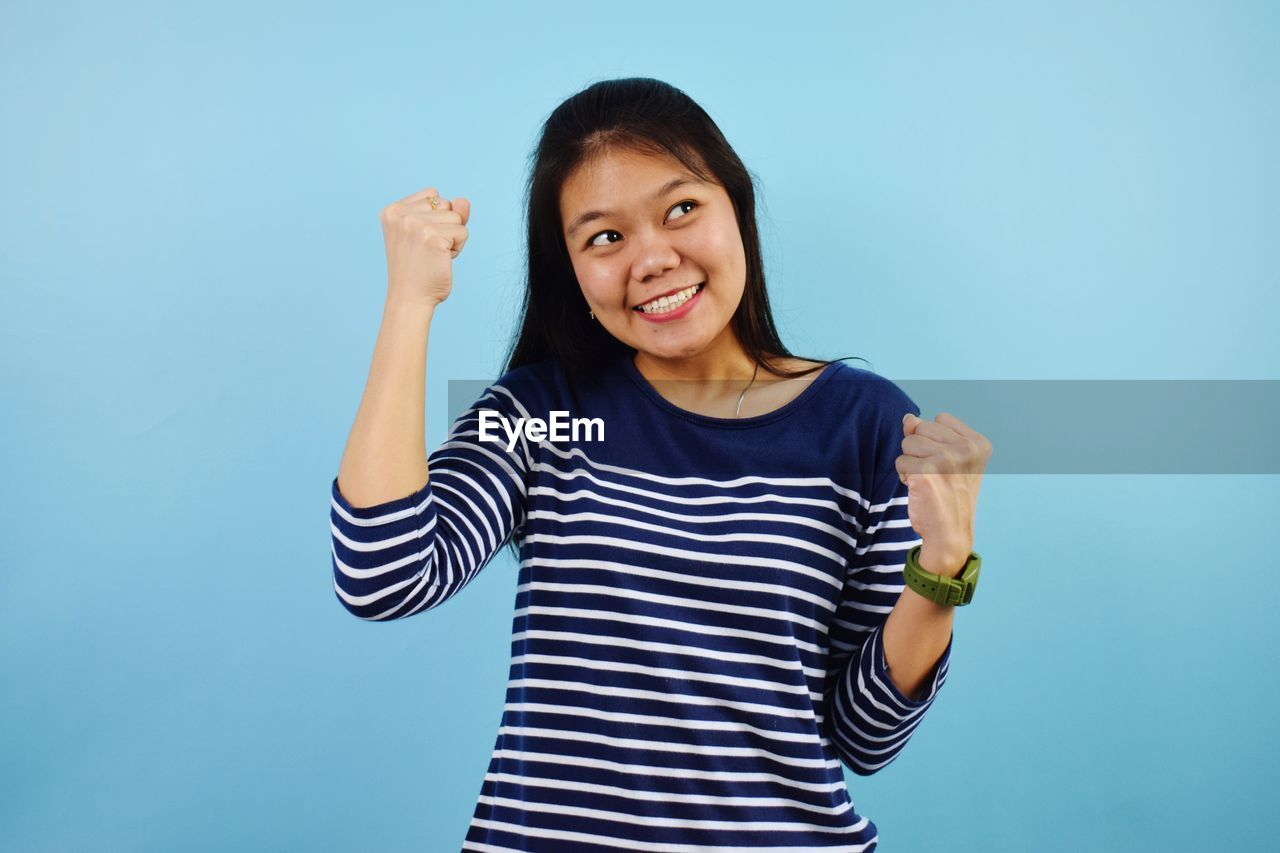 PORTRAIT OF A SMILING YOUNG WOMAN OVER BLUE BACKGROUND