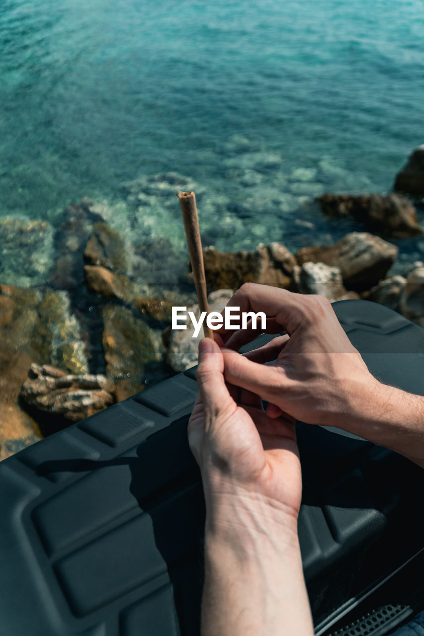 human hand, hand, human body part, water, real people, one person, communication, body part, lifestyles, sea, leisure activity, holding, day, finger, cigarette, bad habit, human finger, outdoors, human limb