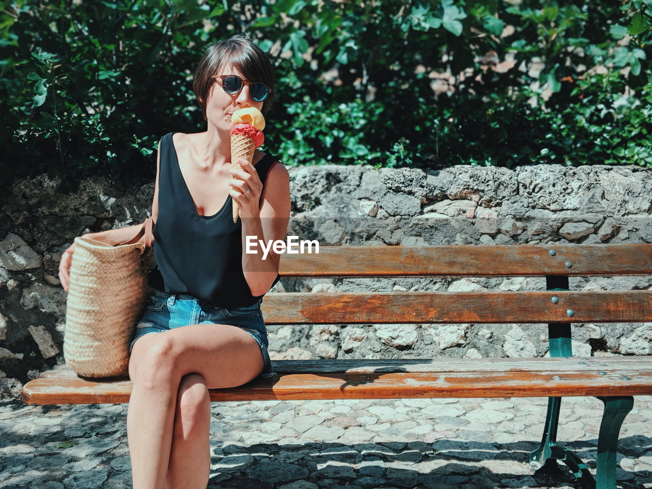 Woman Eating Ice Cream While Sitting On Bench During Sunny Day