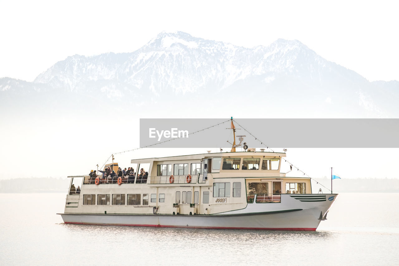 nautical vessel, mode of transportation, transportation, mountain, water, nature, waterfront, day, travel, sea, sky, mountain range, sailing, beauty in nature, outdoors, craft, men, scenics - nature, group of people, passenger craft, cruise ship