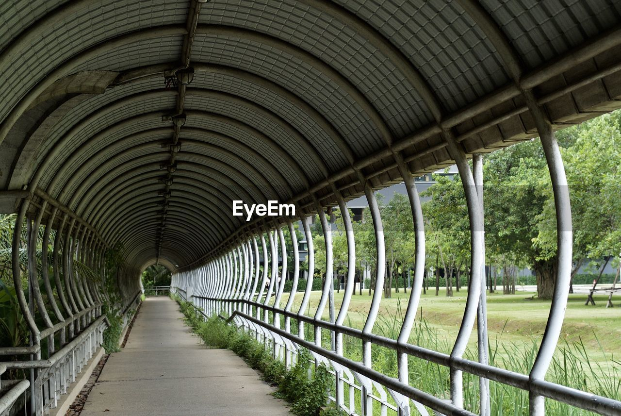 Empty covered footbridge by lawn