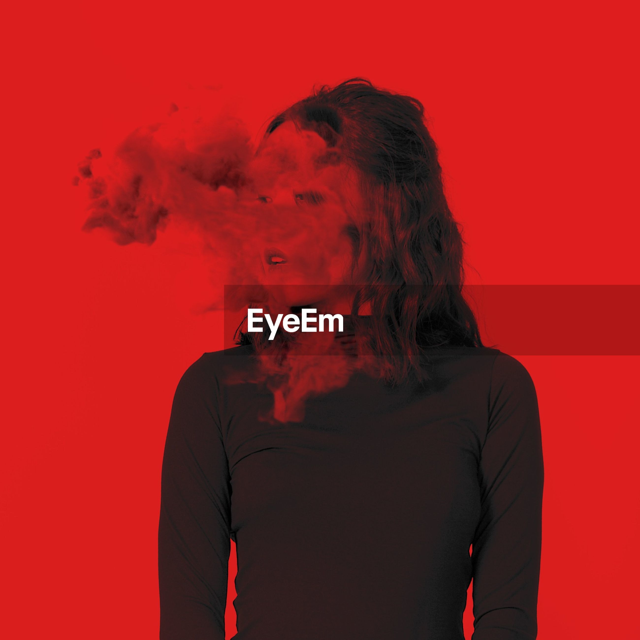 Young woman with smoke standing against red background
