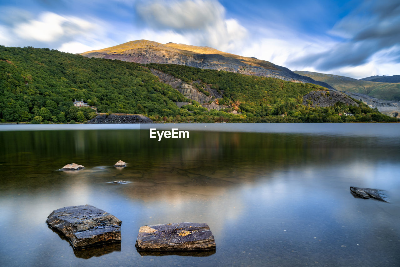 water, mountain, cloud - sky, scenics - nature, beauty in nature, sky, rock, solid, rock - object, lake, tranquility, nature, no people, day, tranquil scene, outdoors, reflection, non-urban scene, idyllic
