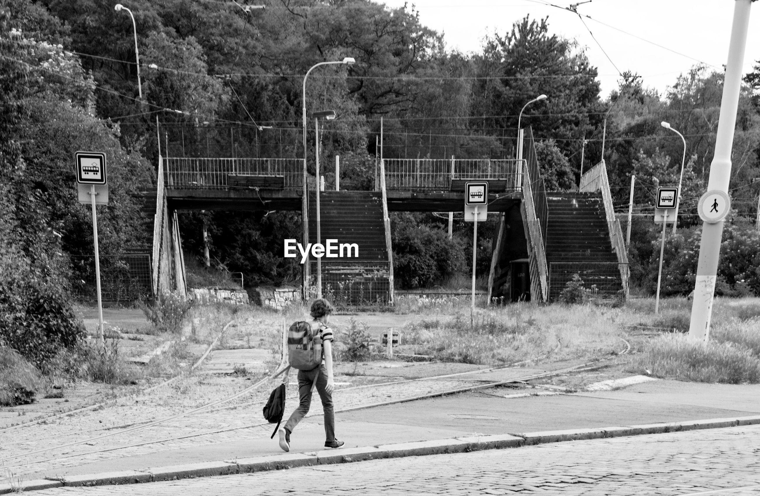 Rear view full length of boy walking on road