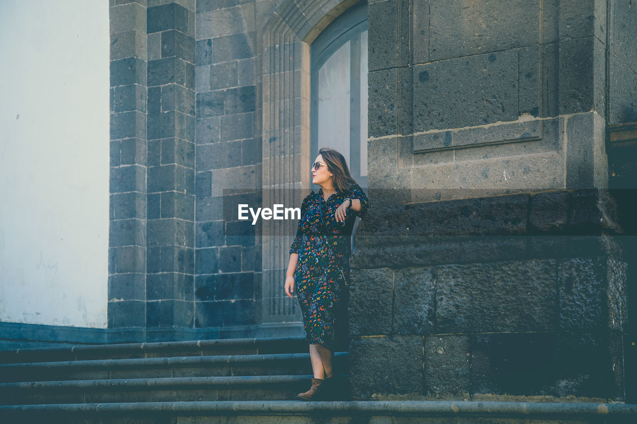 one person, real people, leisure activity, architecture, young adult, lifestyles, young women, built structure, standing, building exterior, full length, casual clothing, women, adult, looking, day, front view, beauty, beautiful woman, fashion, outdoors, hairstyle, contemplation
