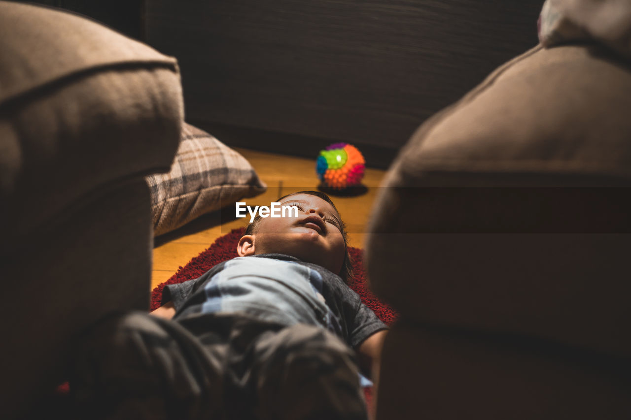 Cute Boy Lying Down On Carpet At Home