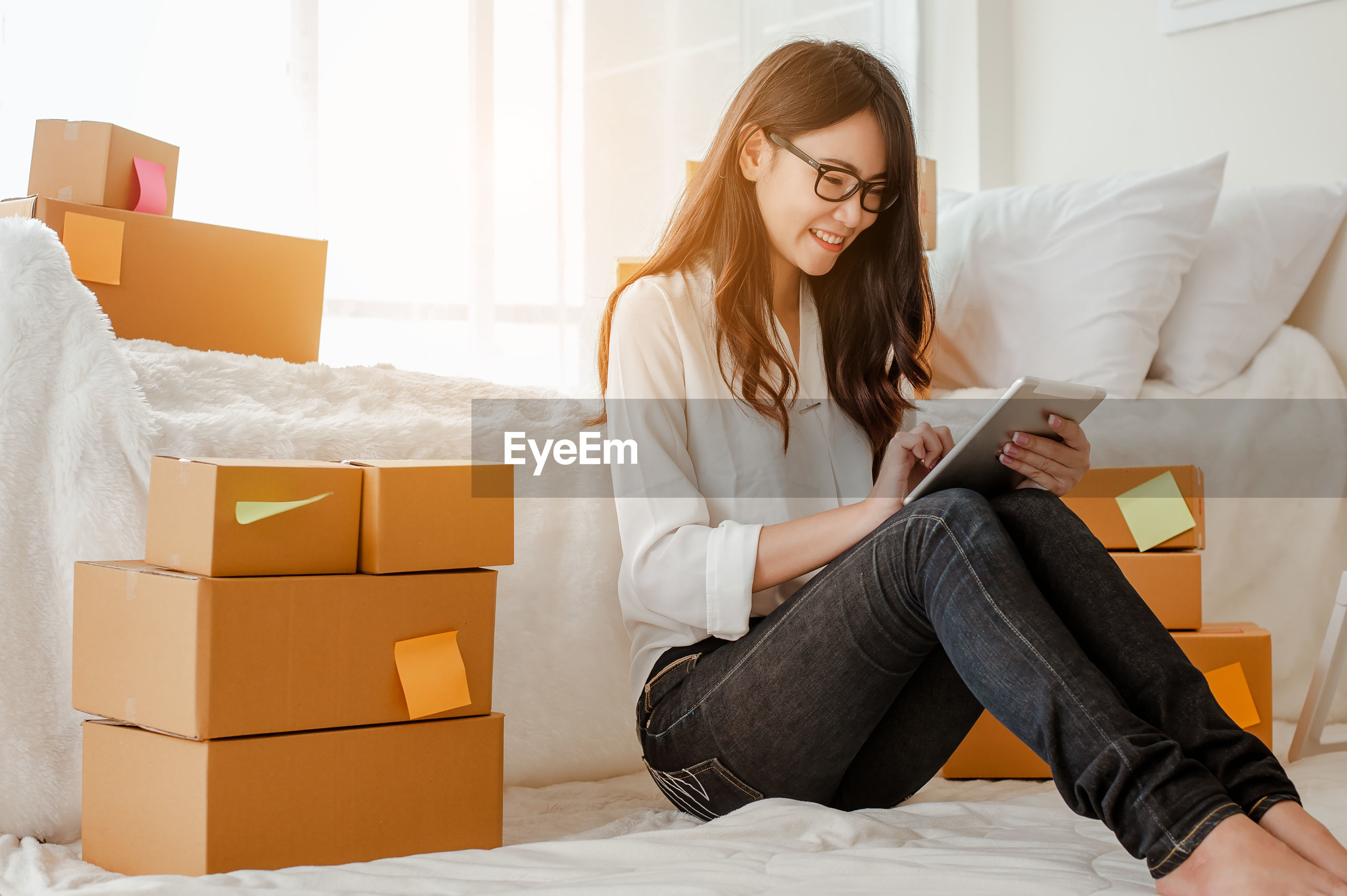 YOUNG WOMAN USING MOBILE PHONE WHILE SITTING IN BOX