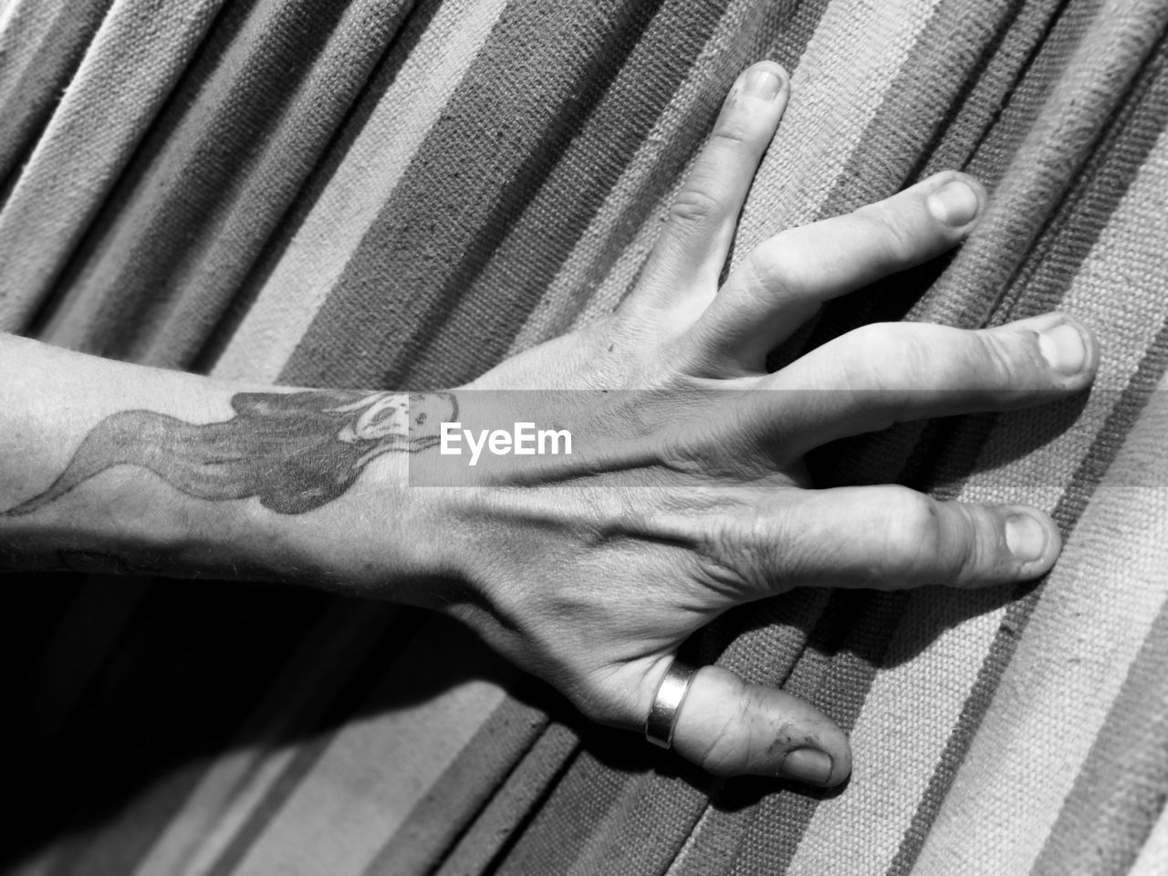 Cropped hand of person with tattoo on bed