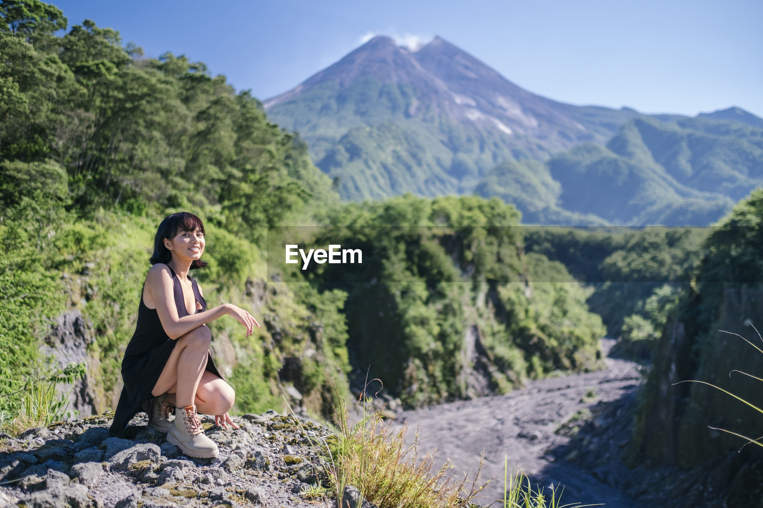 Full length of woman looking away while crouching on rock against mountains and sky