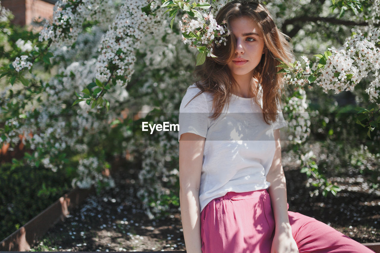 Portrait Of Beautiful Young Woman Standing Against Flower Tree