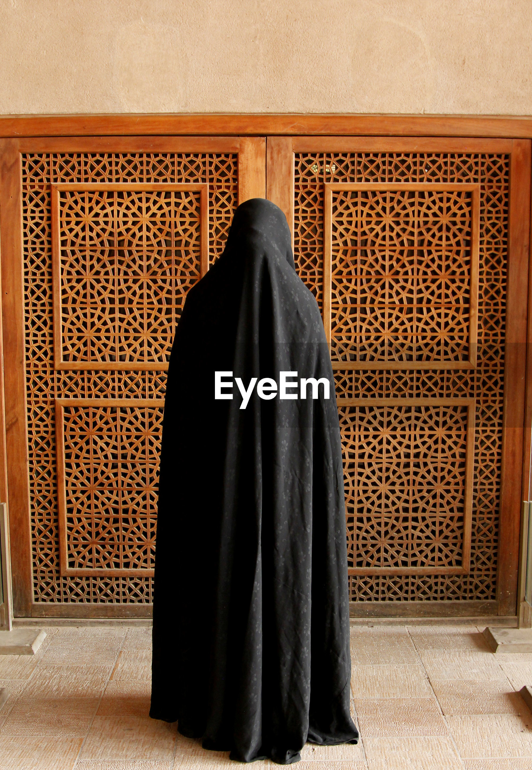 Woman in burka standing against door