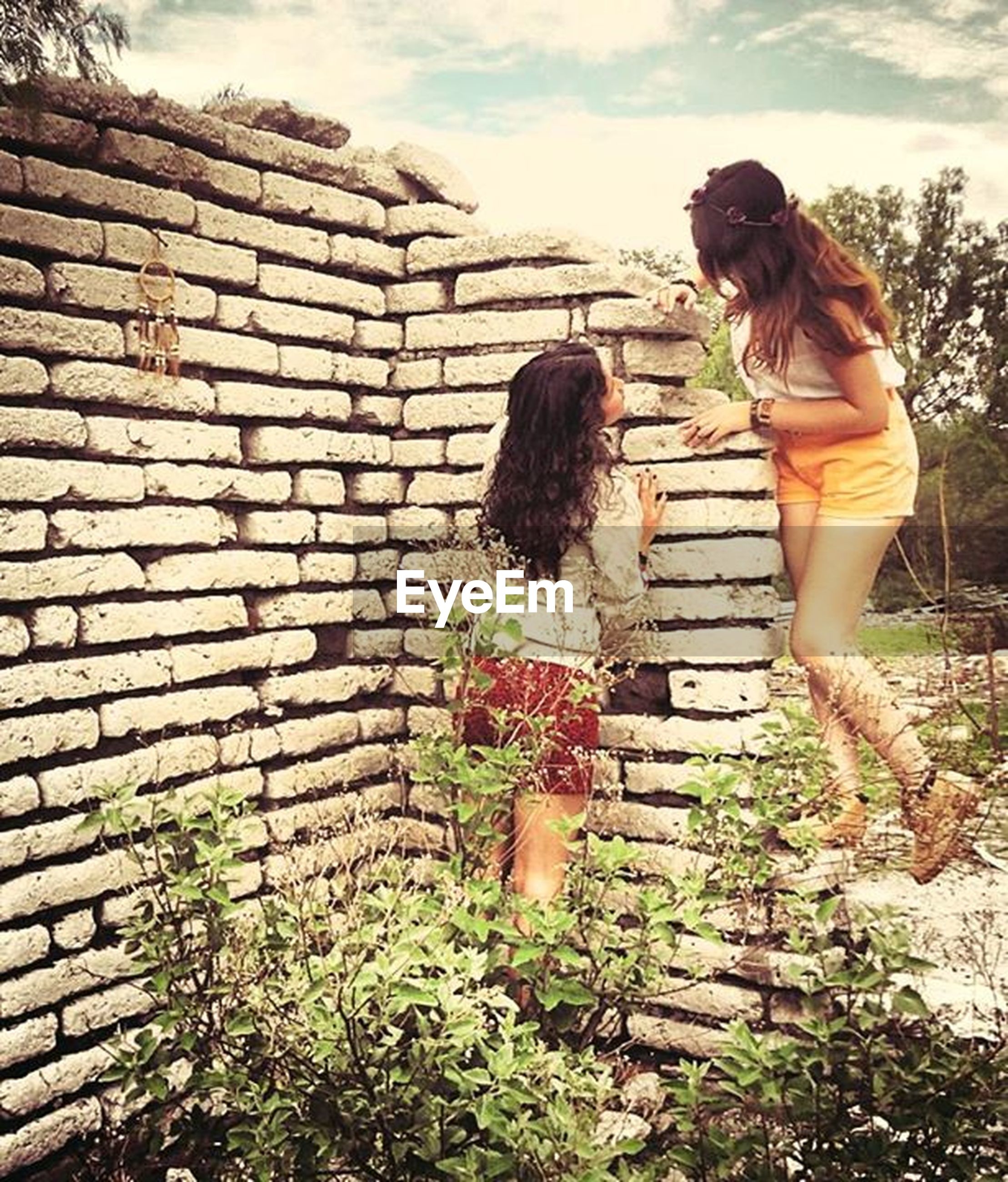 sky, full length, built structure, standing, building exterior, architecture, cloud - sky, lifestyles, plant, day, leisure activity, low angle view, wall - building feature, outdoors, casual clothing, rear view, brick wall, three quarter length