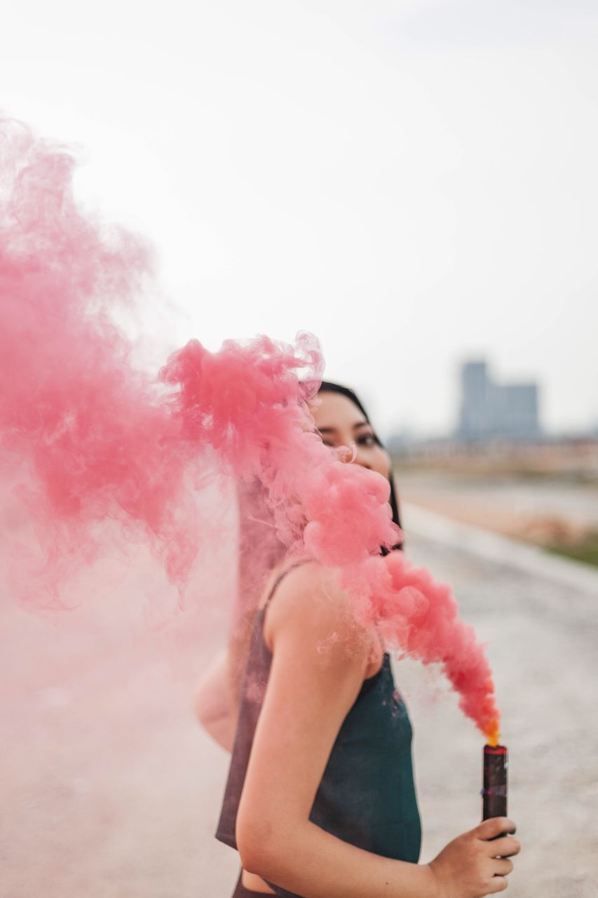 one person, lifestyles, pink color, copy space, leisure activity, real people, holding, sky, focus on foreground, day, women, young adult, nature, smoke - physical structure, front view, three quarter length, adult, young women, outdoors, beautiful woman, teenager