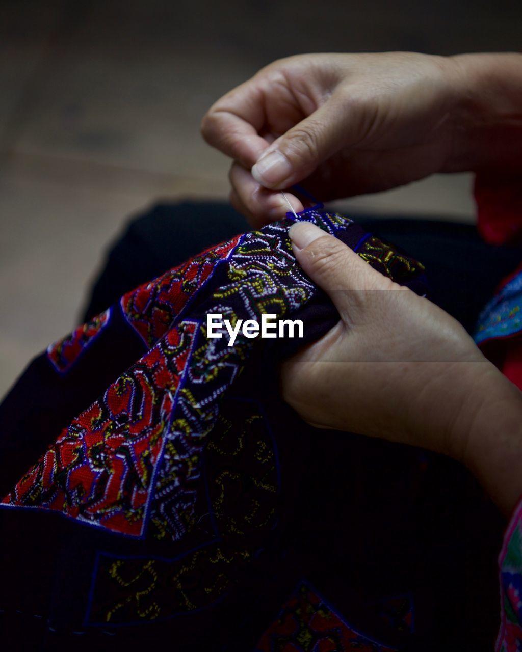 High angle view of woman stitching fabric