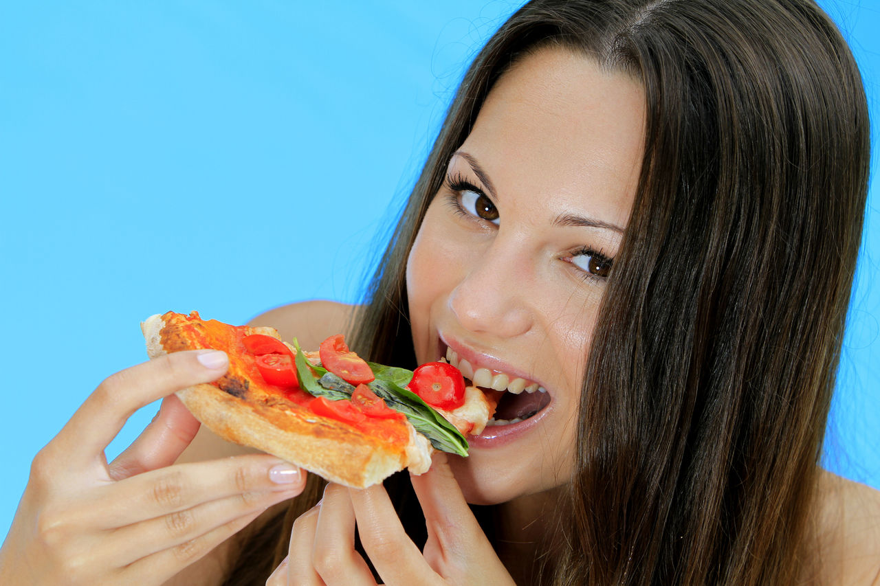 Portrait of smiling young woman eating pizza against blue background