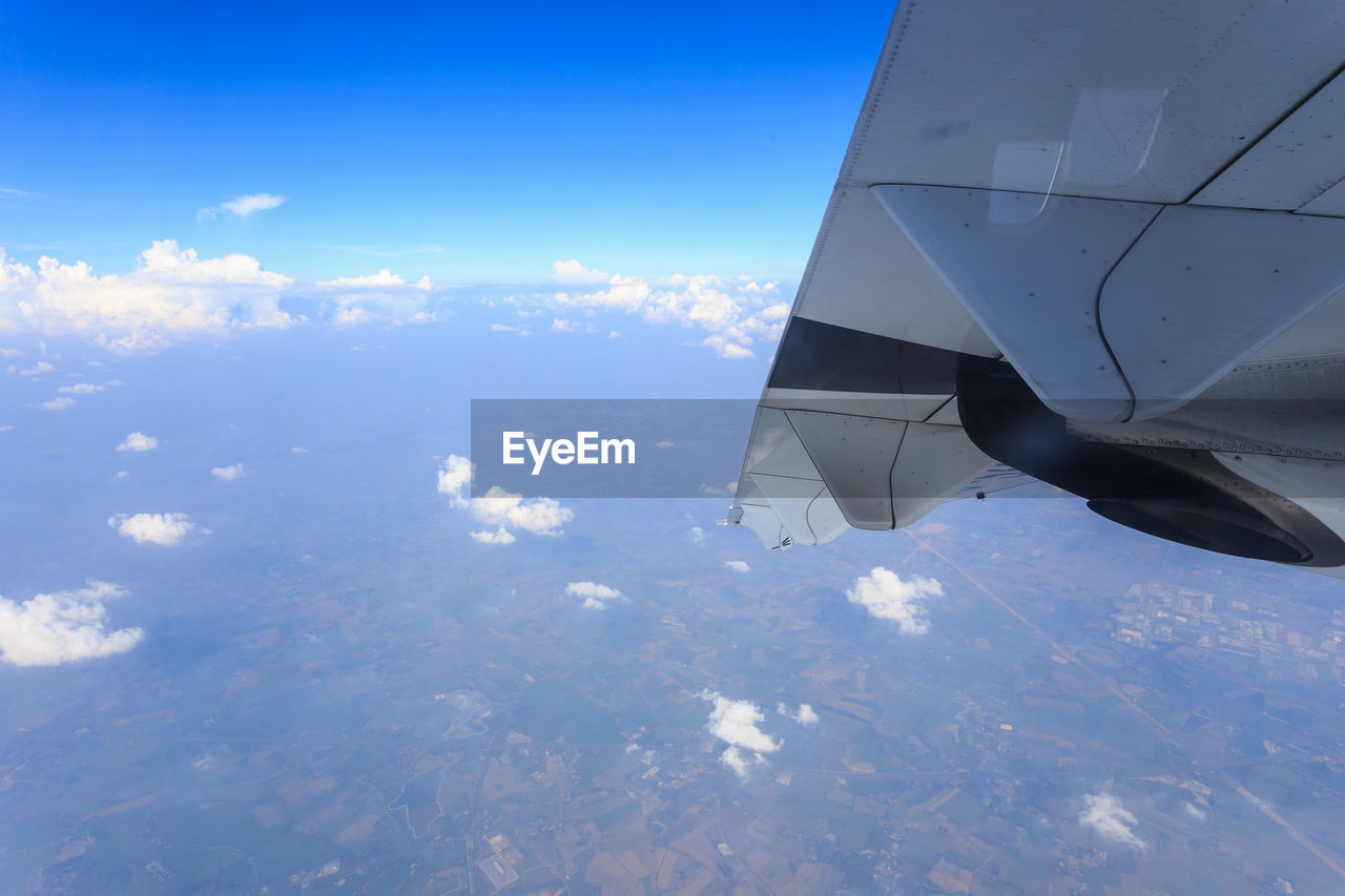 cloud - sky, airplane, air vehicle, sky, mode of transportation, beauty in nature, transportation, mid-air, no people, nature, day, scenics - nature, aerial view, aircraft wing, flying, motion, travel, on the move, outdoors, blue