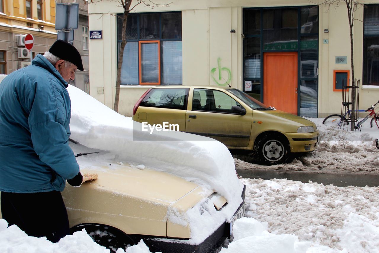 mode of transportation, architecture, motor vehicle, car, winter, land vehicle, transportation, real people, men, built structure, building exterior, snow, cold temperature, day, city, people, standing, working, warm clothing