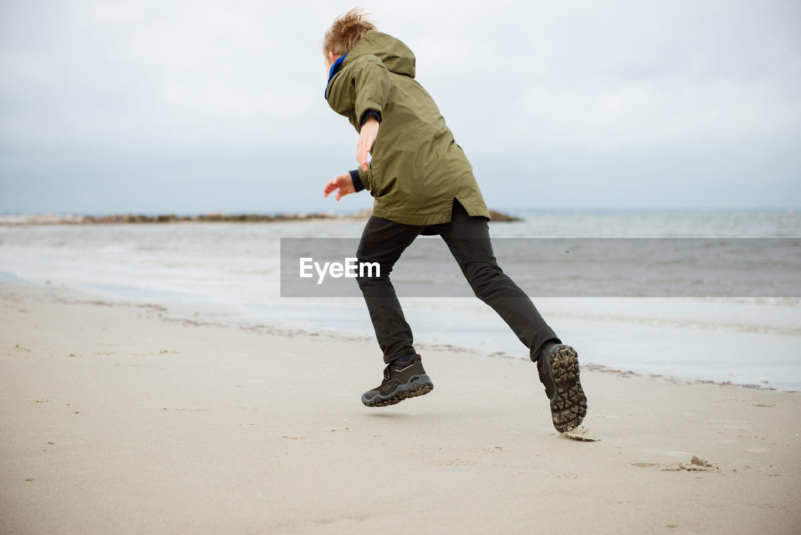 Rear view full length of boy running at beach