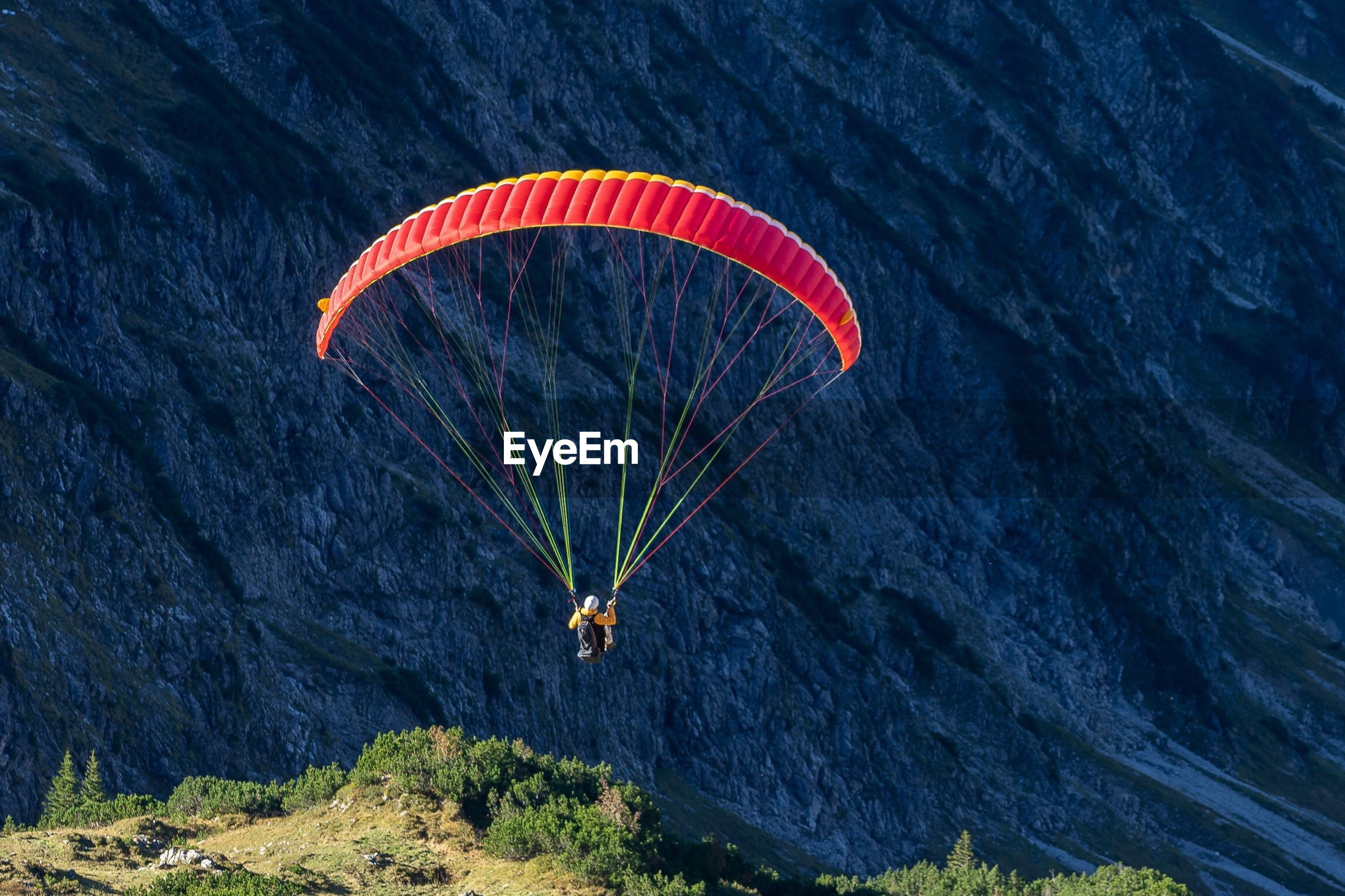 Person paragliding against mountain