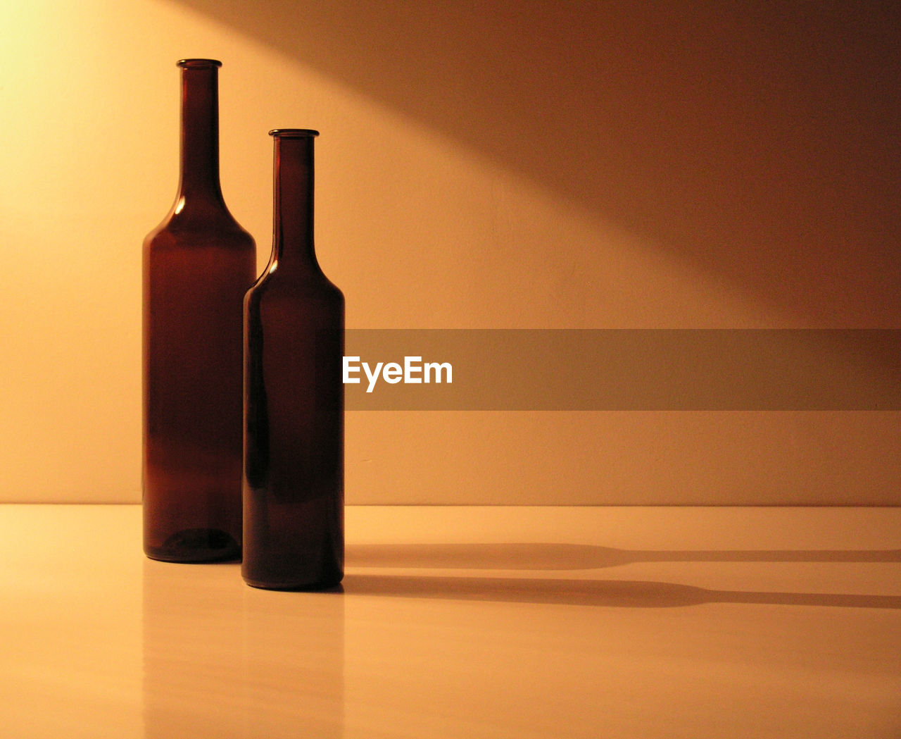 still life, indoors, bottle, no people, table, container, food and drink, glass - material, wall - building feature, copy space, empty, reflection, food, drink, side by side, shadow, freshness, alcohol, single object, close-up, blank
