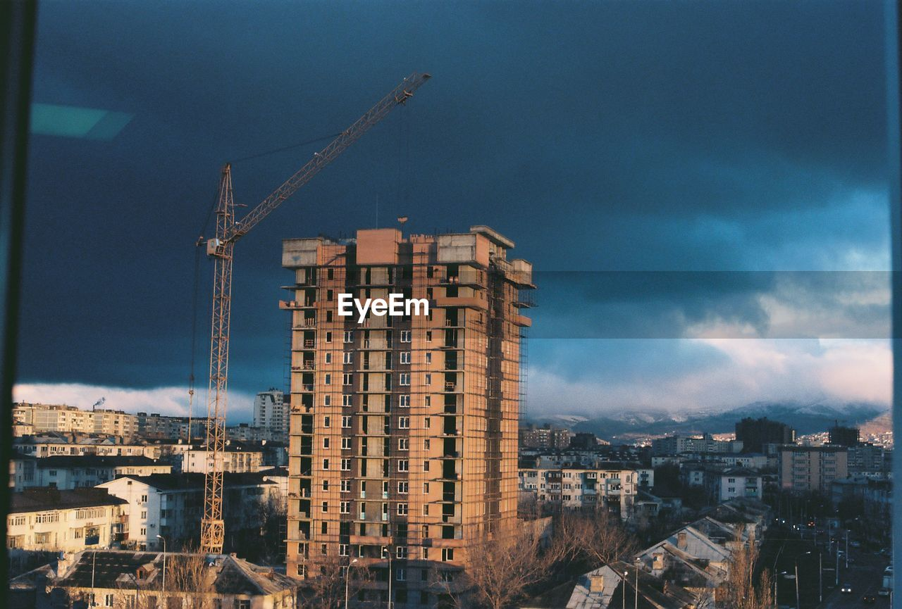 Building And Crane Against Cloudy Sky In City