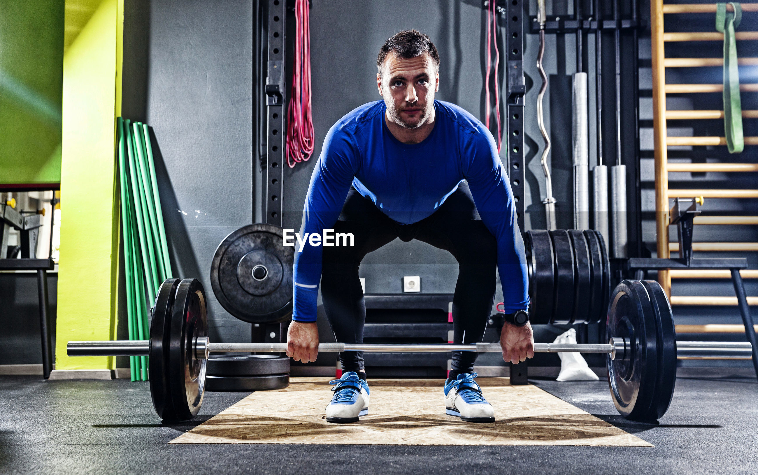 Young man weightlifting at gym