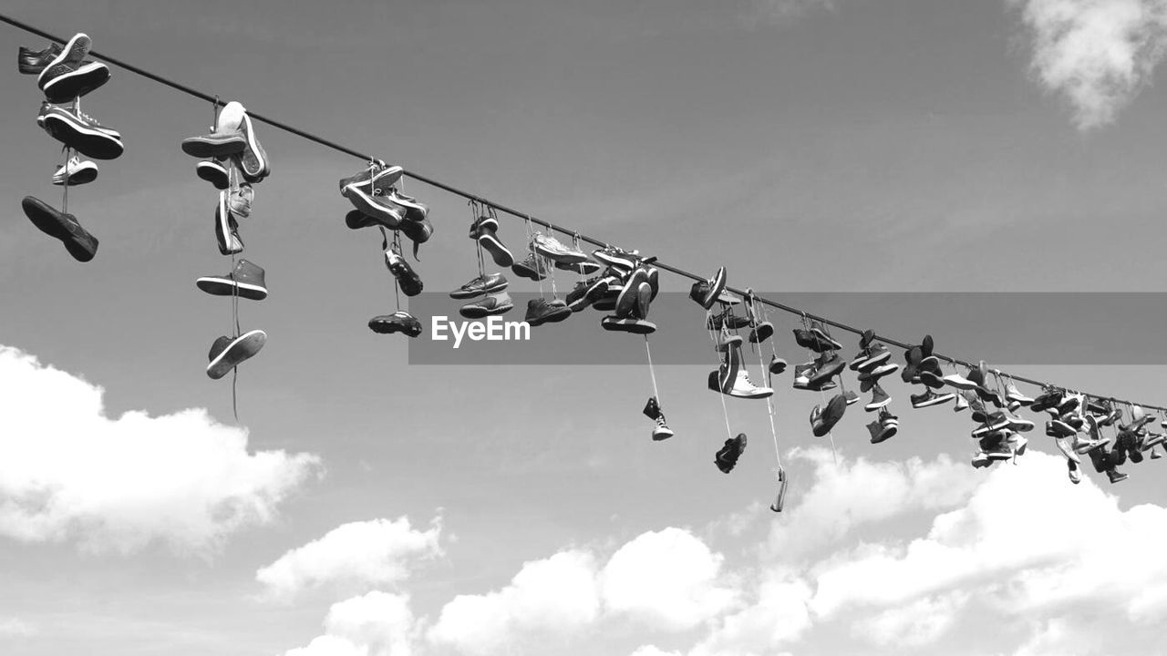 Low Angle View Of Shoes Hanging Against Sky