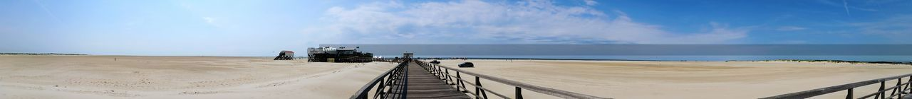 Panoramic view of pier on beach against sky