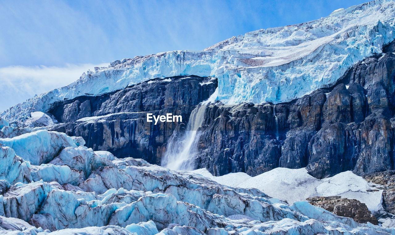 Glacier On Rocky Mountain Against Sky