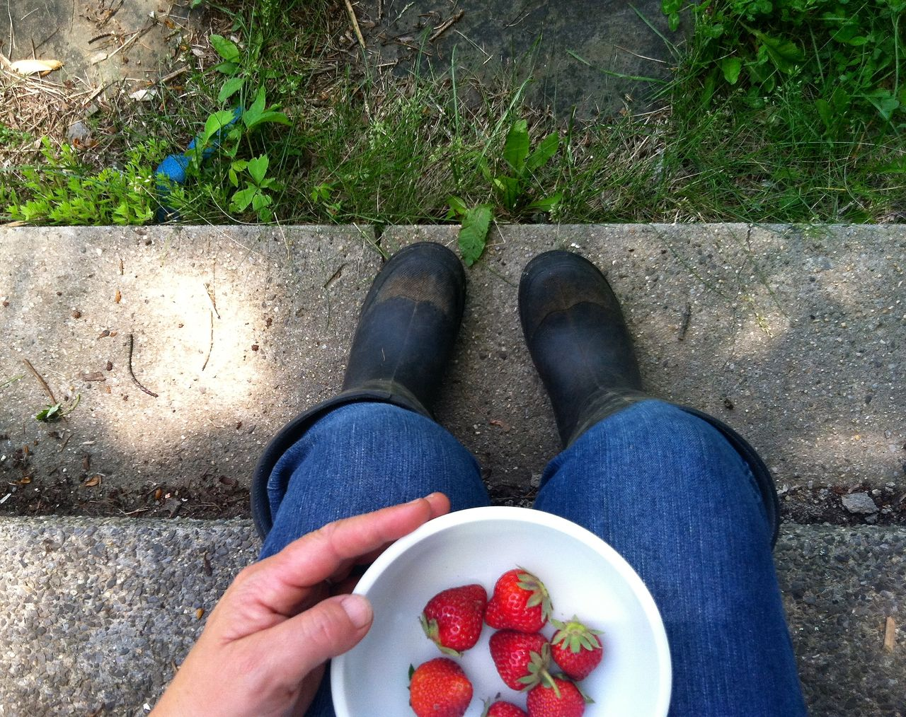 Low section of person with strawberries in bowl sitting on steps
