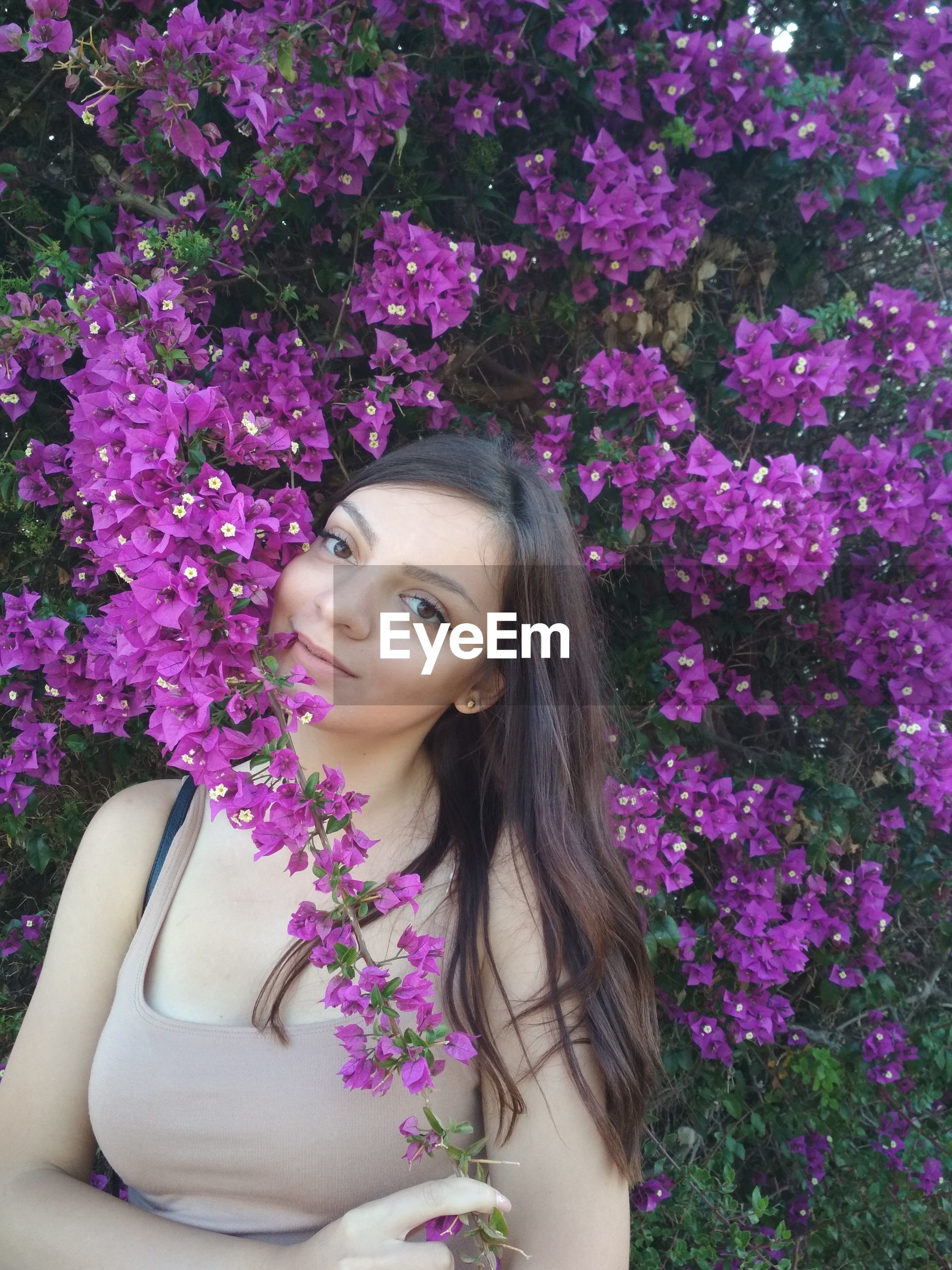 Portrait of young woman against purple flowering plants