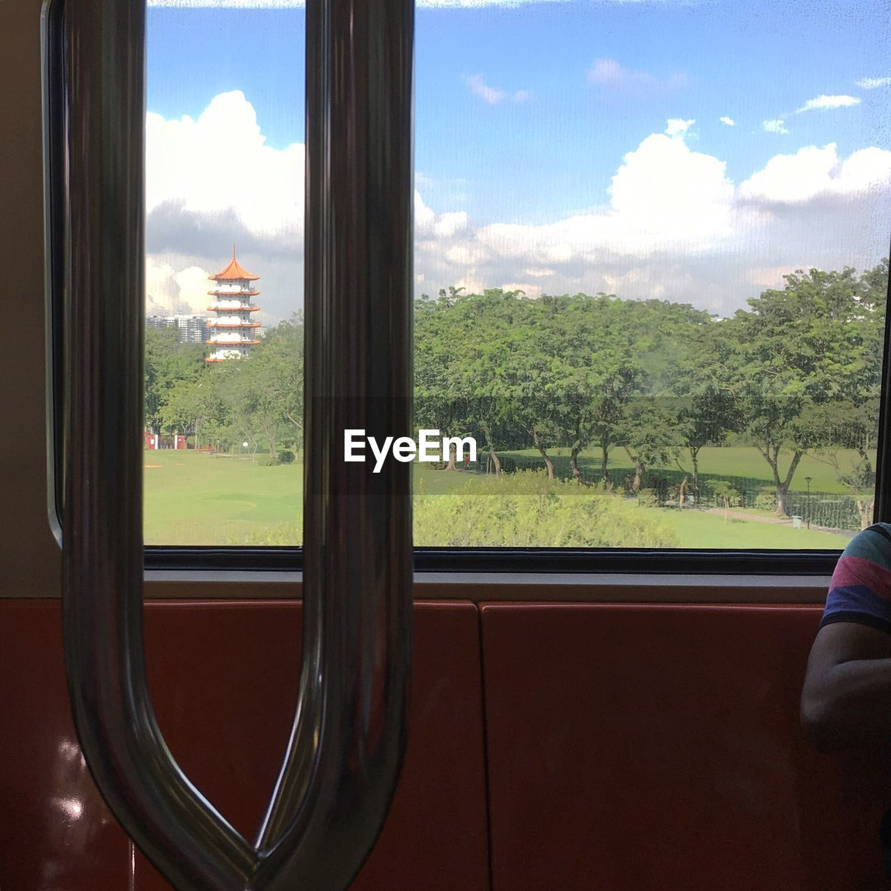 window, glass - material, vehicle interior, sky, transportation, cloud - sky, day, tree, real people, indoors, train - vehicle, land vehicle, one person, mountain, nature, close-up, people