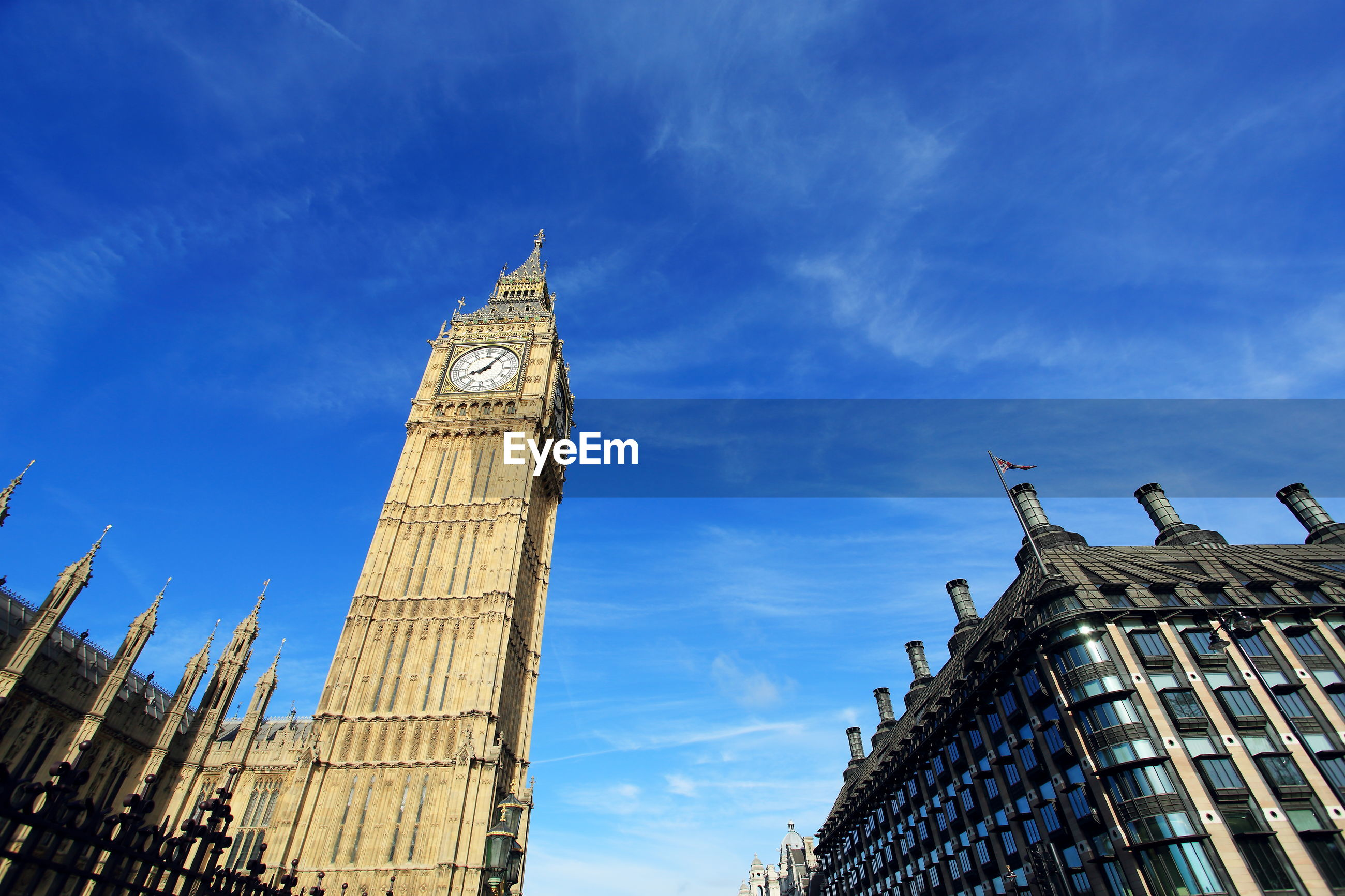 Low angle view of big ben against blue sky in city