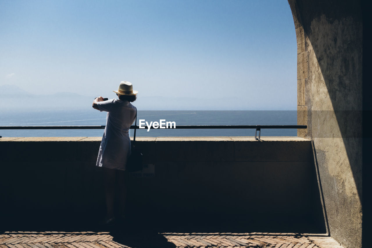 Full Length Rear View Of Woman Photographing Sea From Observation Point Against Clear Sky