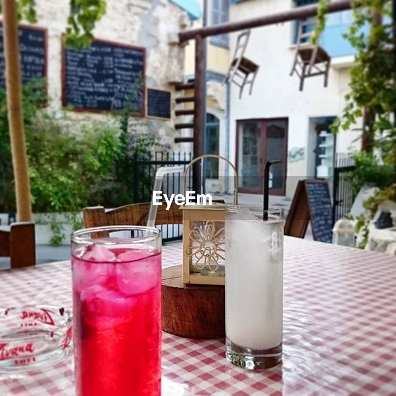 refreshment, drink, drinking glass, table, food and drink, no people, drinking straw, focus on foreground, architecture, day, outdoors, building exterior, cafe, close-up, red, water, freshness