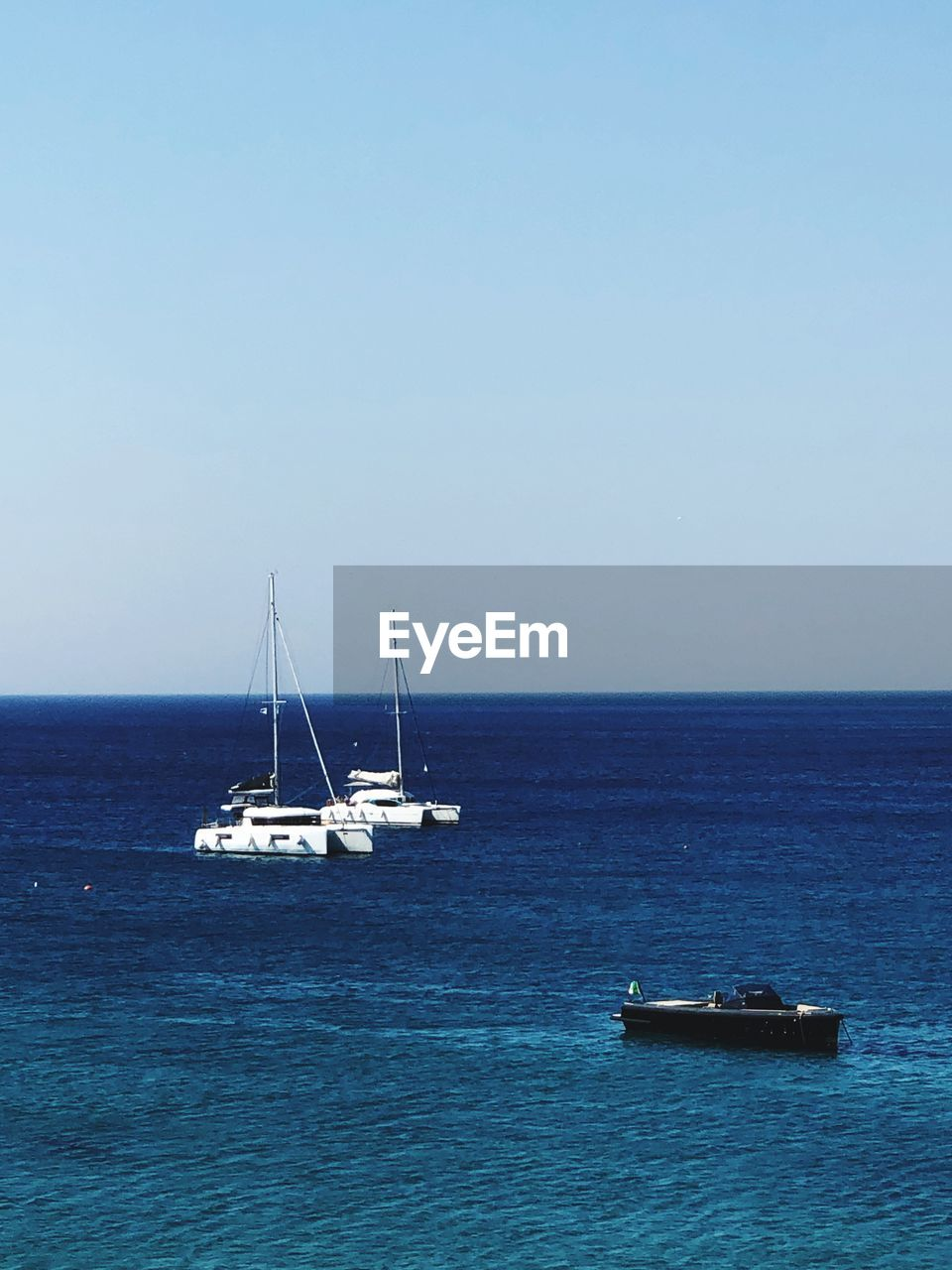 sea, water, nautical vessel, transportation, sky, horizon over water, mode of transportation, horizon, beauty in nature, sailboat, scenics - nature, waterfront, copy space, clear sky, no people, nature, tranquil scene, sailing, tranquility, outdoors, yacht, anchored