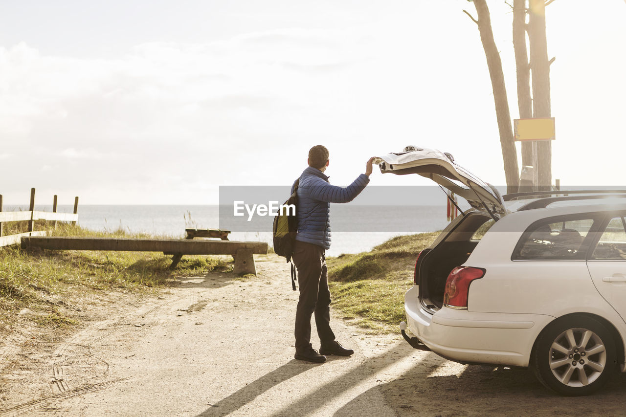 FULL LENGTH REAR VIEW OF MAN STANDING ON CAR AGAINST SKY