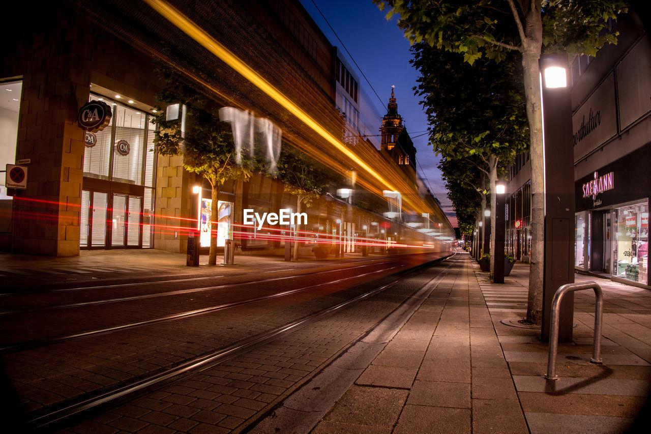 LIGHT TRAILS ON ILLUMINATED STREET AT NIGHT