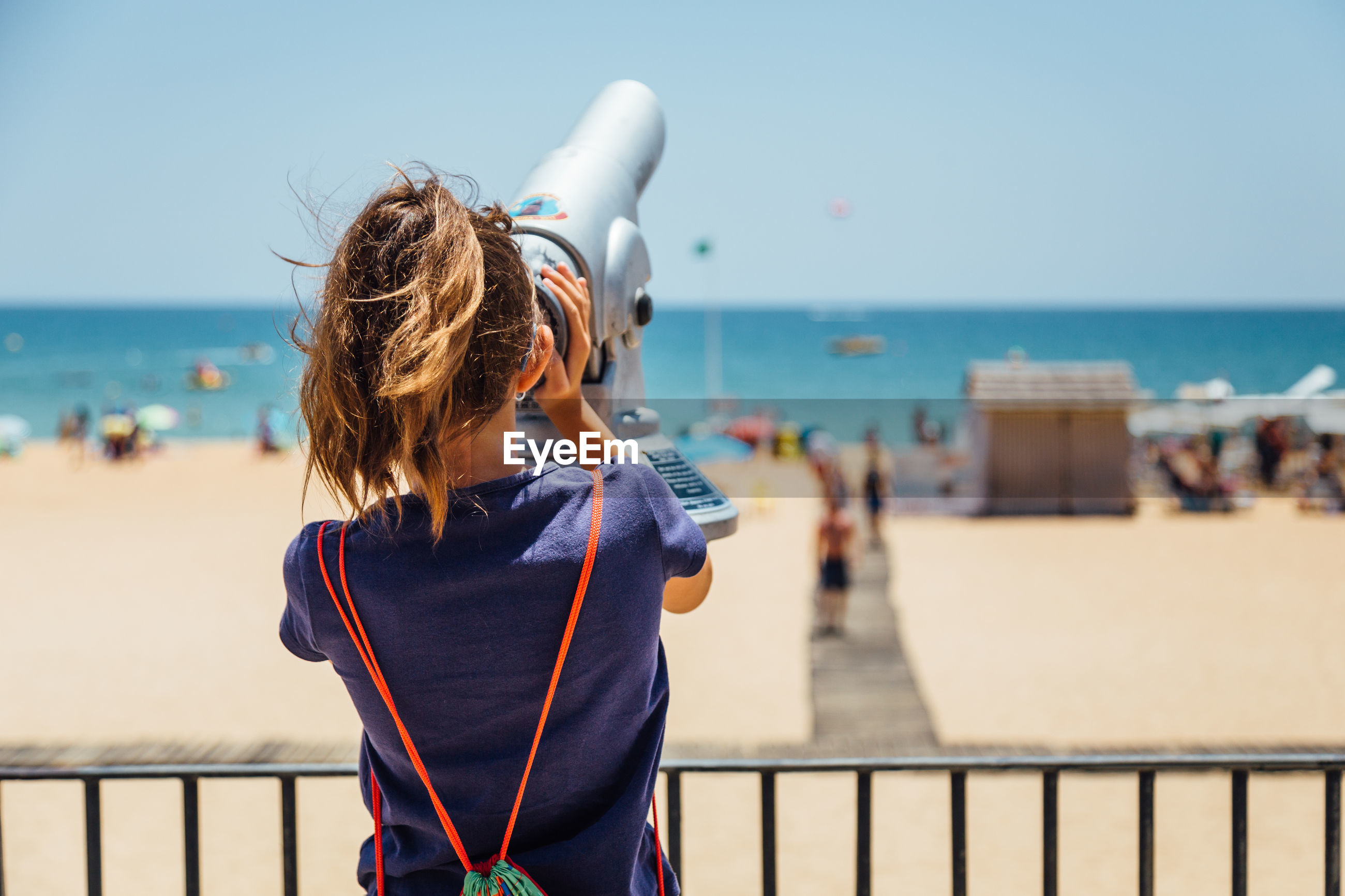 Rear view of woman looking through coin operated binoculars at beach