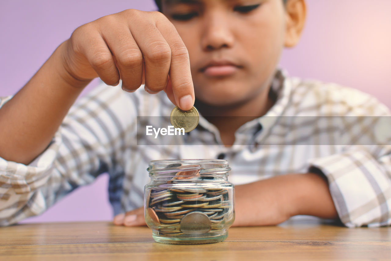 Close-Up Of Boy Putting Coin In Piggy Bank At Table Against Wall