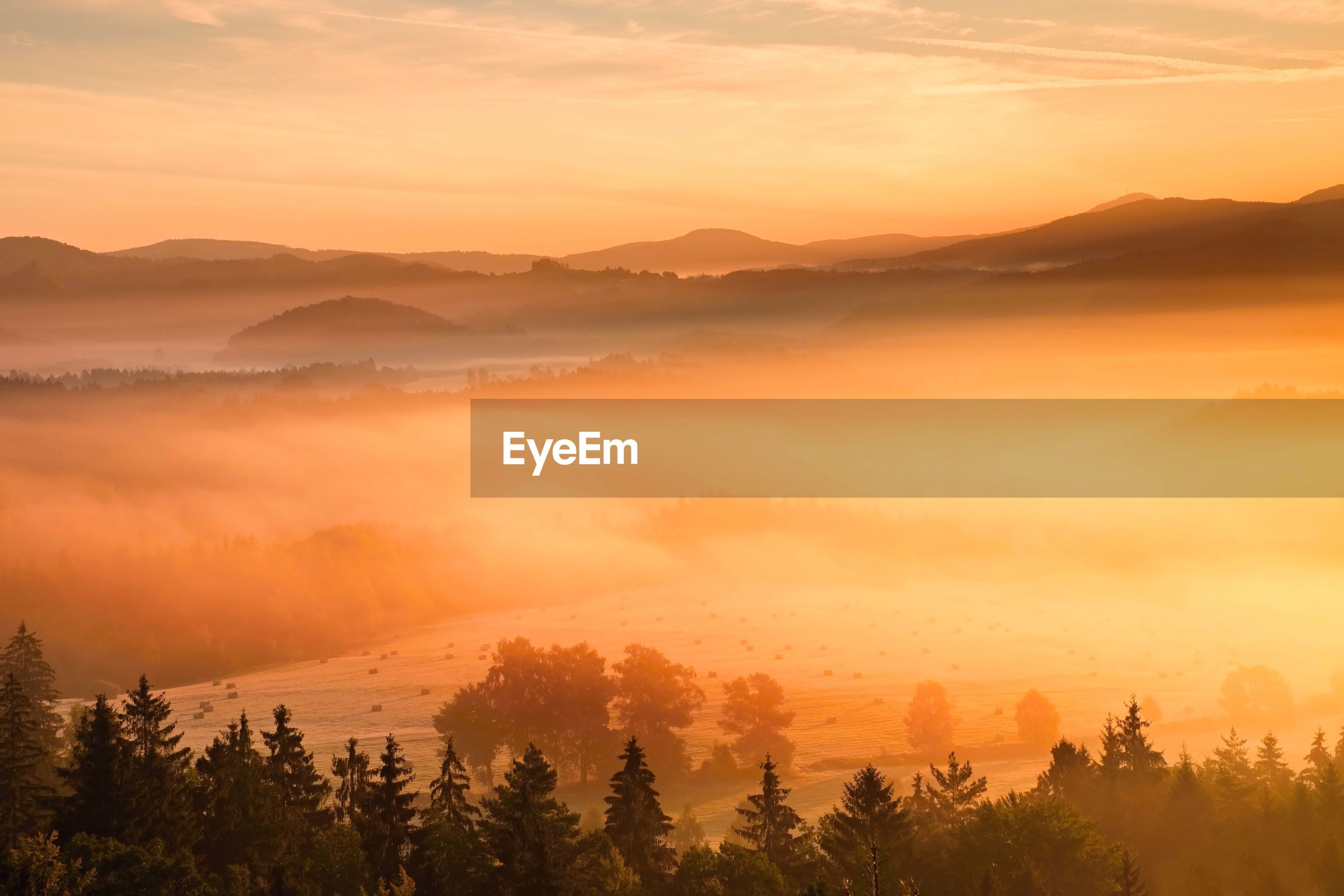 Pink daybreak in hilly landcape. autumn misty morning in a beautiful hills. peaks of hill are in fog