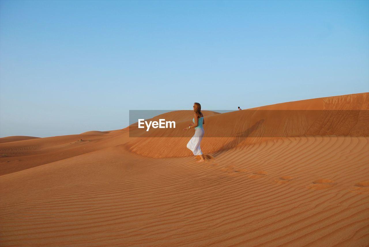 Woman walking on sand dune in desert against clear sky