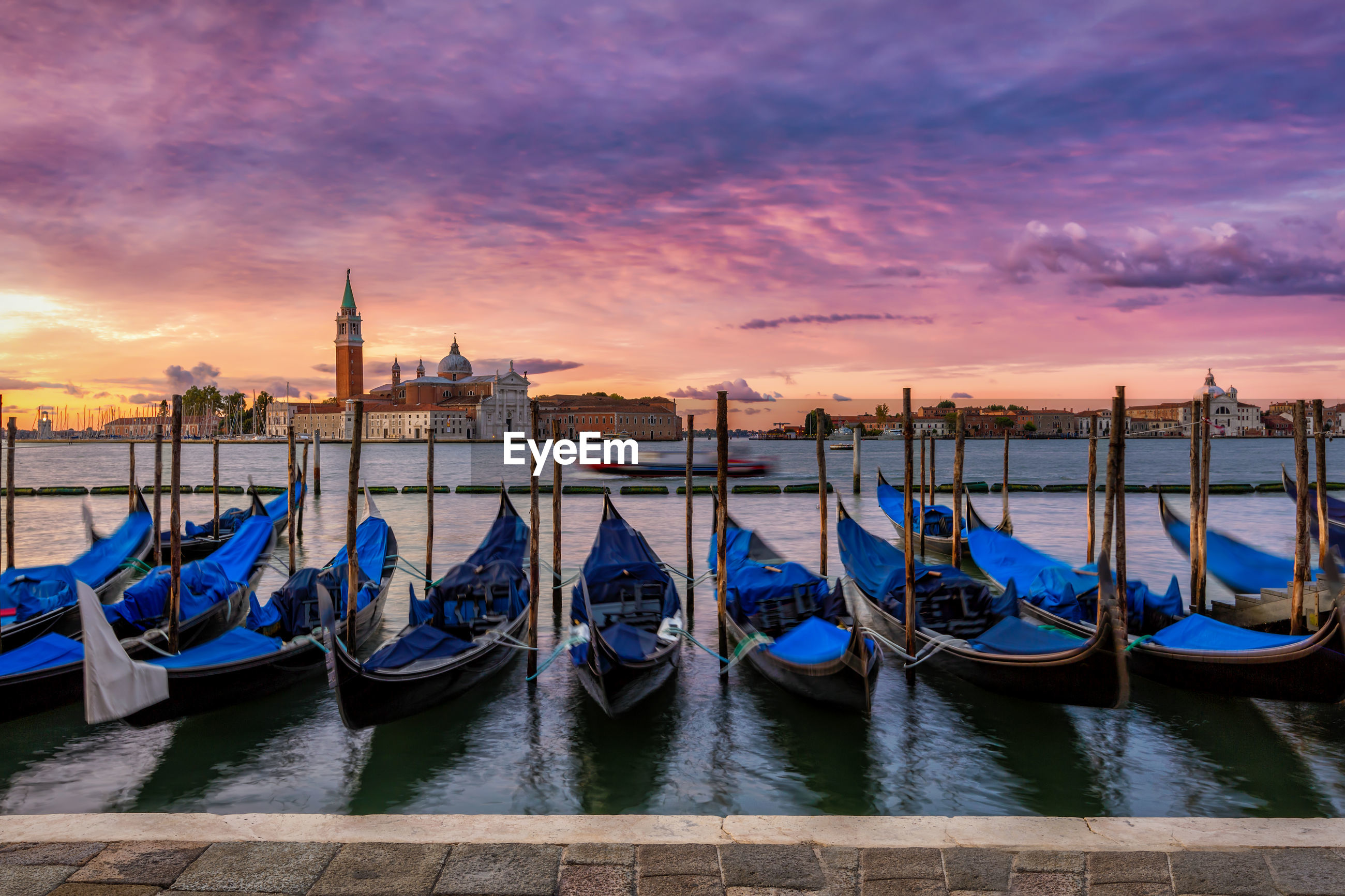 View of boats moored in city at sunset
